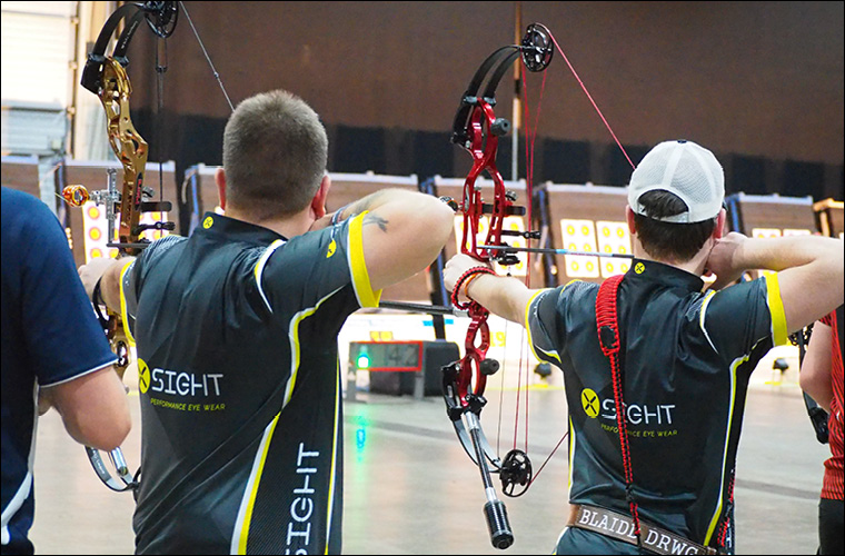 two compound archers wearing x sight shirts and glasses