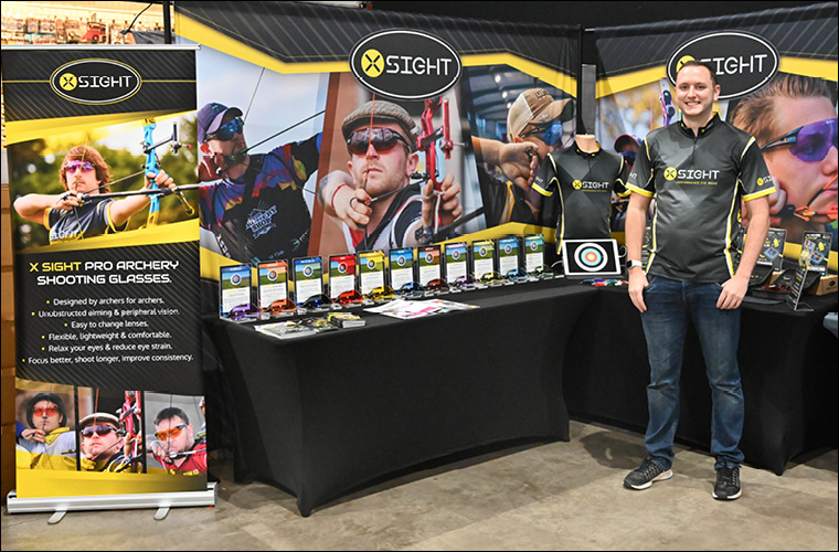 Jack Harris from X Sight archery standing proudly in front of the X Sight archery trade show stand at 2018 Indoor Nationals exhibiting archery specific performance glasses