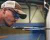 compound archer wearing x sight archery shooting glasses to score arrows during an indoor archery competition