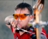 Compound archer wearing X Sight glasses aiming at the target