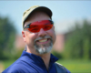 Man wearing red lens x sight archery glasses smiling at the camera