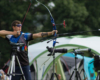 recurve archer stood on the shooting line at full draw with his bow ready to shoot the target wearing his x sight archery glasses